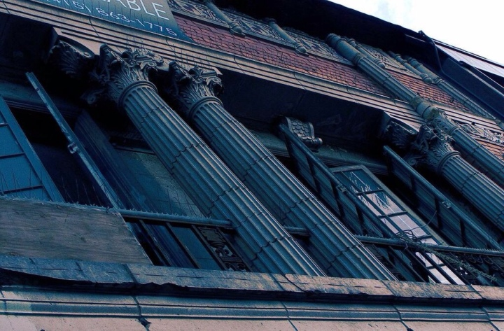 Looking up at an old building with columns and wrought iron faux balconies on the boarded-up windows